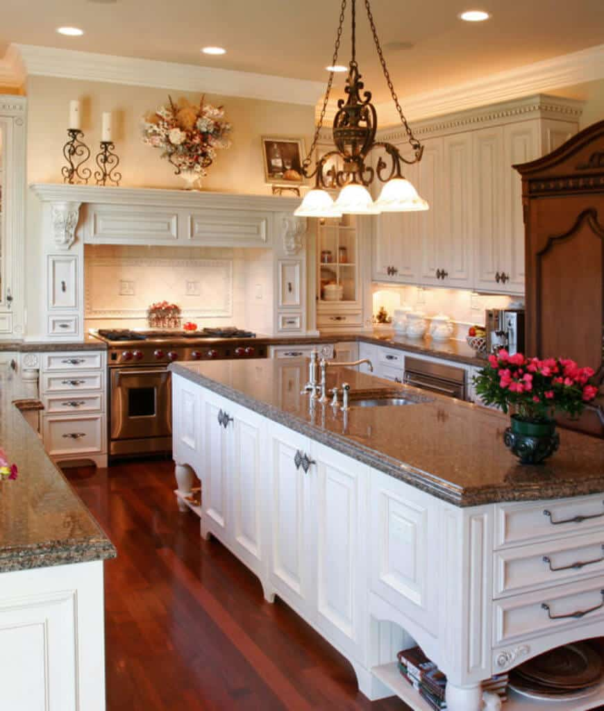 Classy kitchen offers white cabinetry that matches with the island bar fitted with a sink and chrome fixtures. It is illuminated by dome chandelier and recessed ceiling lights.