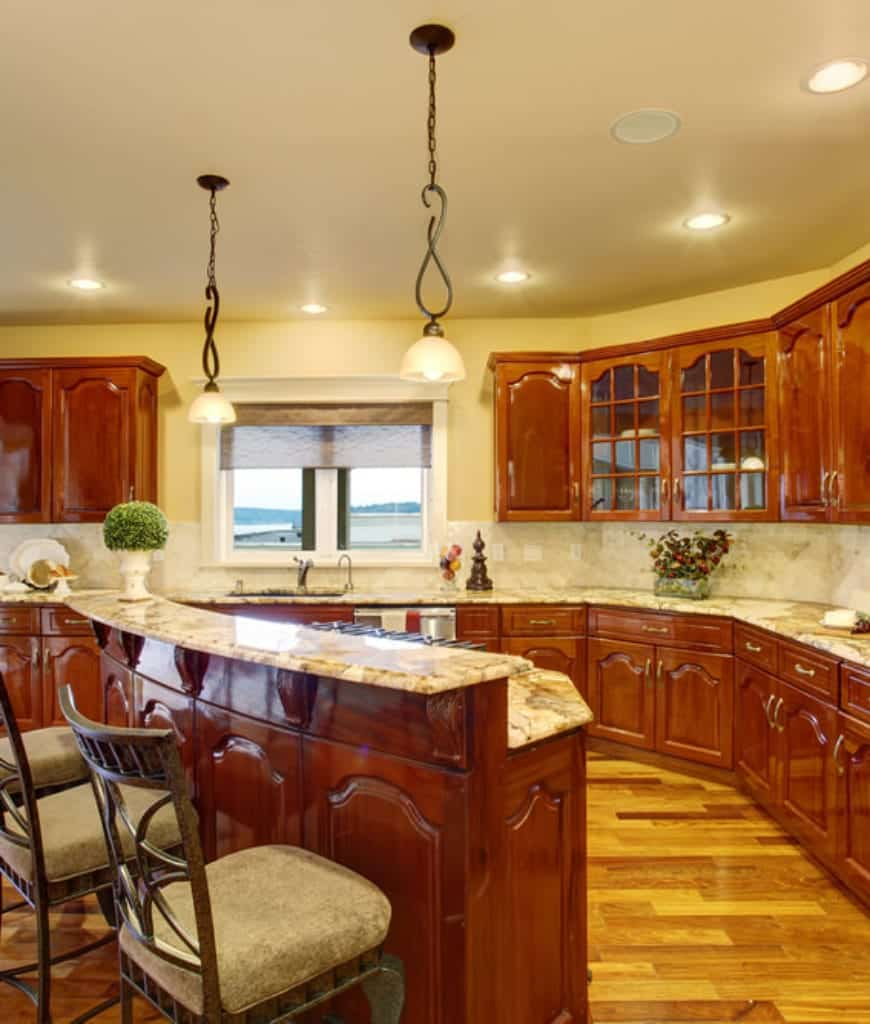 Cozy kitchen with a two-tier breakfast bar surrounded by matching cabinetry and cushioned counter chairs. It includes glass dome pendants and glazed windows covered with a translucent roman shade.