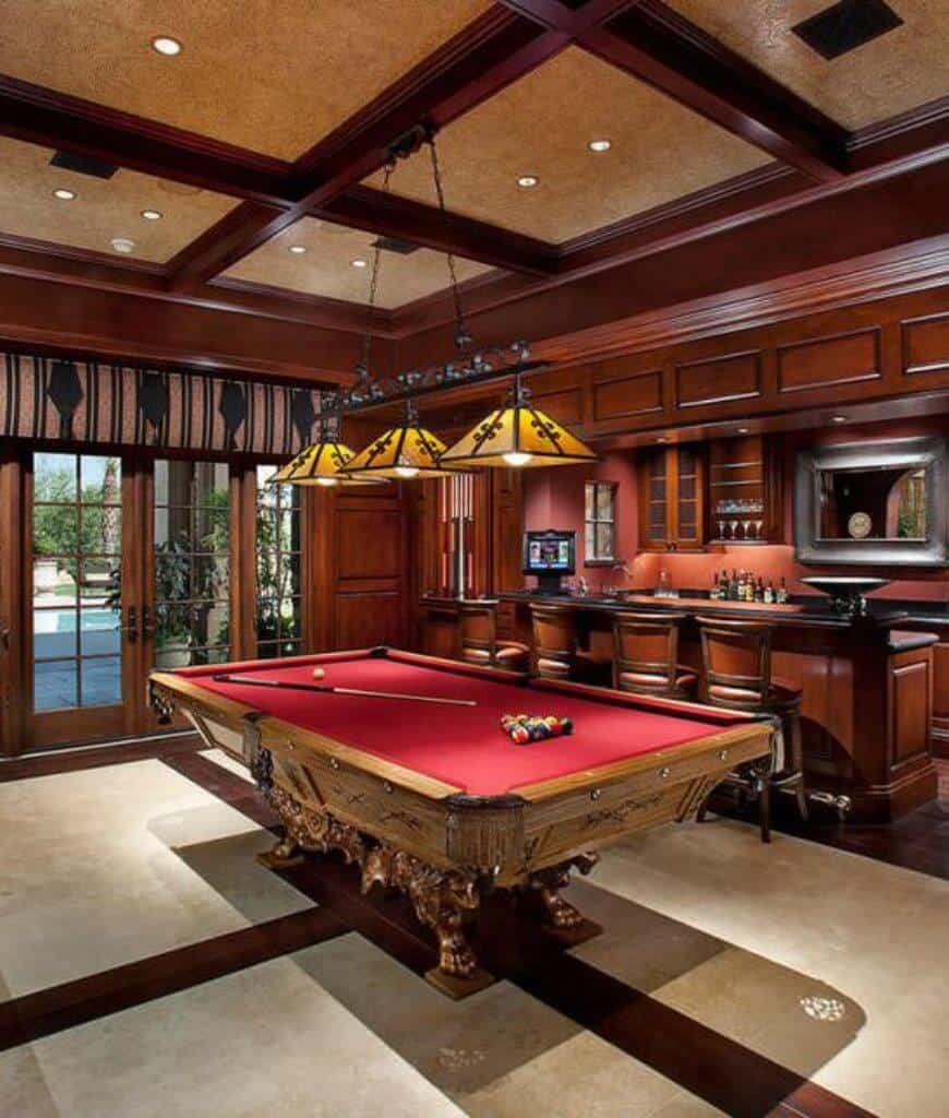 Sophisticated man cave with an ornate clawfoot pool table across the bar area sporting a unified look. It is lighted by yellow pendants that hung from the coffered ceiling.