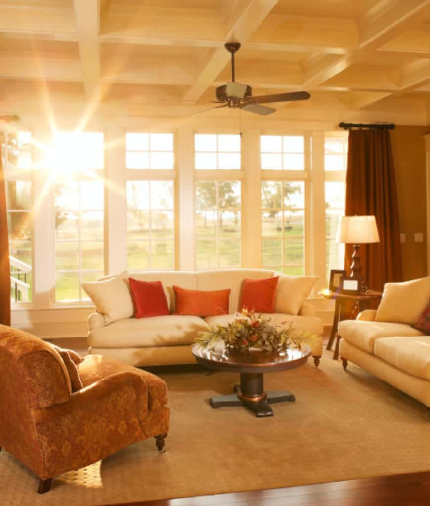 The bright living room showcases a brown armchair and round coffee table that sit on the velvet rug along with a white sofa accented with orange pillows.