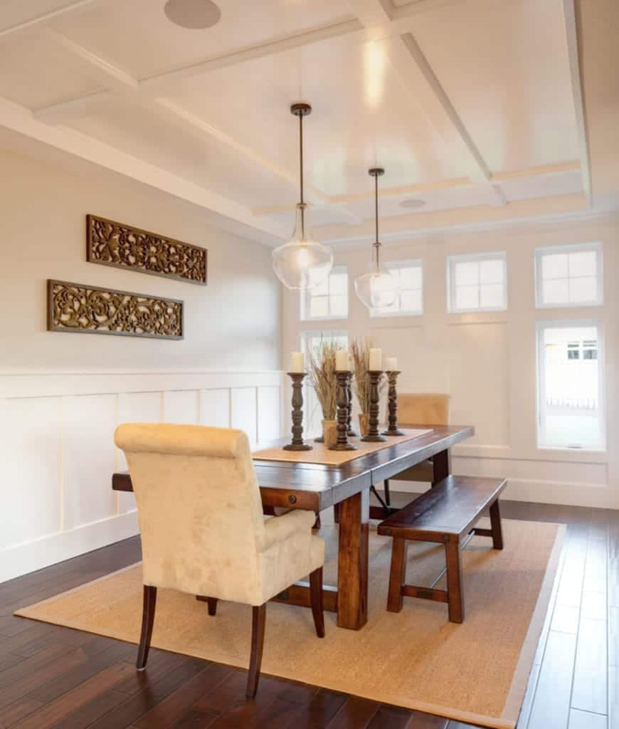 White dining room designed with carved wood wall arts and glass pendant lights that hung from the coffered ceiling. It has a wooden dining table surrounded with matching benches and velvet chairs that sit on a jute rug.