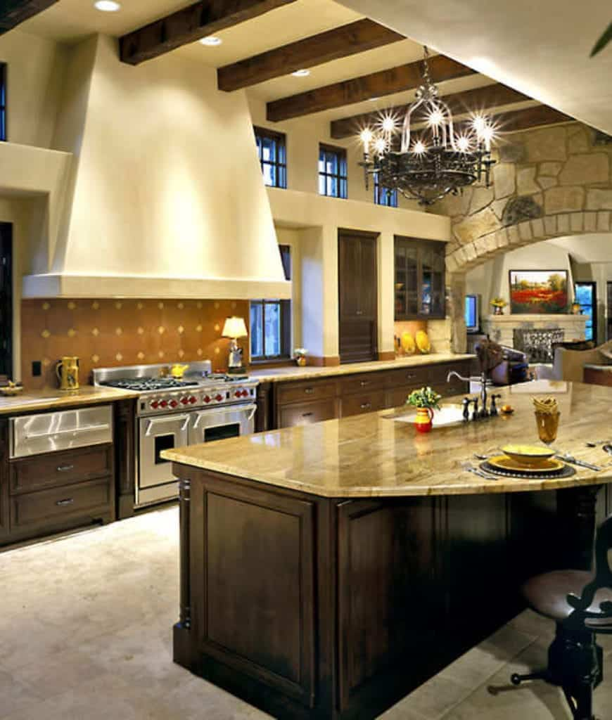 A wrought iron chandelier that hung from the wood beam ceiling illuminates this kitchen boasting wooden cabinetry and stainless steel range accented with dotted backsplash.