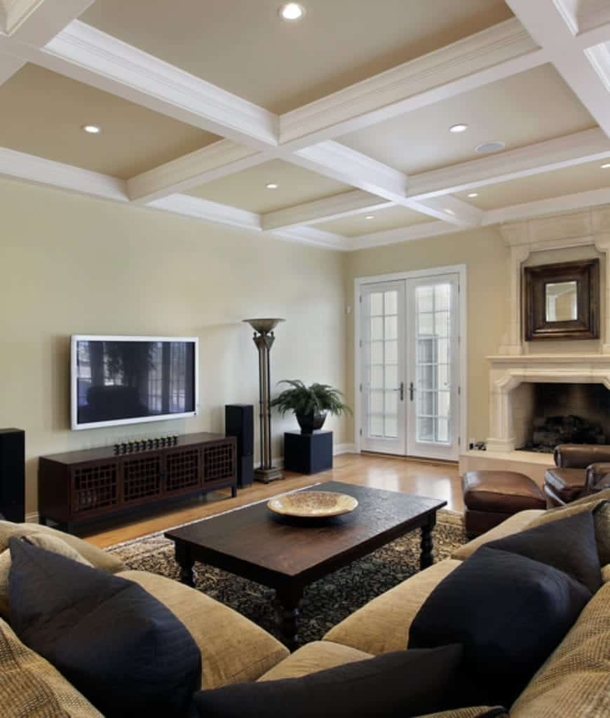 Black fluffy pillows lay on the tan sectional in this living room with a wooden coffee table and leather lounge chair across the fireplace topped with a wooden framed mirror.
