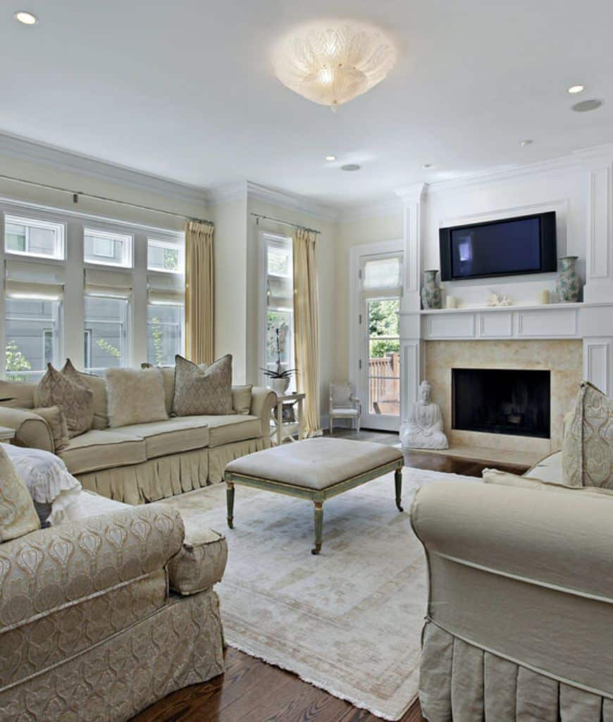 Classy living room features a leather ottoman that sits on an area rug surrounded with beige sectionals. It includes a television mounted above the fireplace that's accented with a white sculpture.
