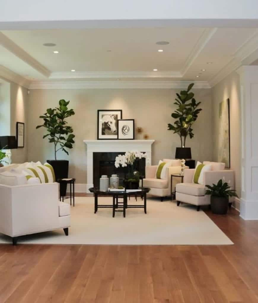 White living room boasts sleek sofas and chairs along with a fireplace accented with fiddle leaf fig plants that add a refreshing ambiance to the room.