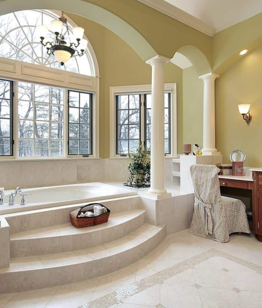 Natural light streams through the framed windows in this primary bathroom boasting an alcove bathtub lined with white columns. There's a wooden vanity on the side that's paired with a skirted chair.