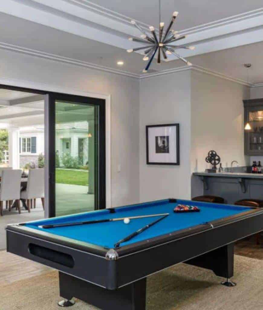 Contemporary room illuminated by a statement chandelier that hung over the blue pool table sitting on a beige area rug. It includes a bar area and a slider that opens to the patio.