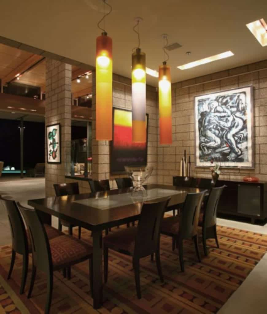 Warm dining room decorated with interesting wall arts and cylindrical pendants that hung over the black dining set that sits on a patterned rug.