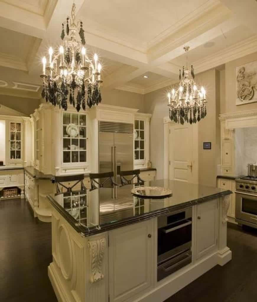 Luxury kitchen with glass front cabinets and a white kitchen island fitted with an oven and lighted by a pair of fabulous chandeliers that hung from the coffered ceiling.