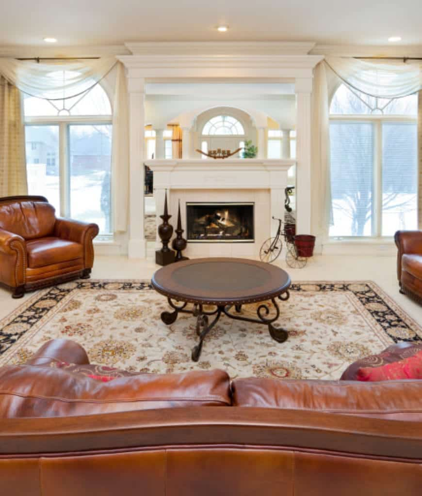 White living room boasts a fireplace in between arched glass windows wrapped in sheer valences. It includes a brown leather sofa set and a round coffee table that sits on a classy floral rug.