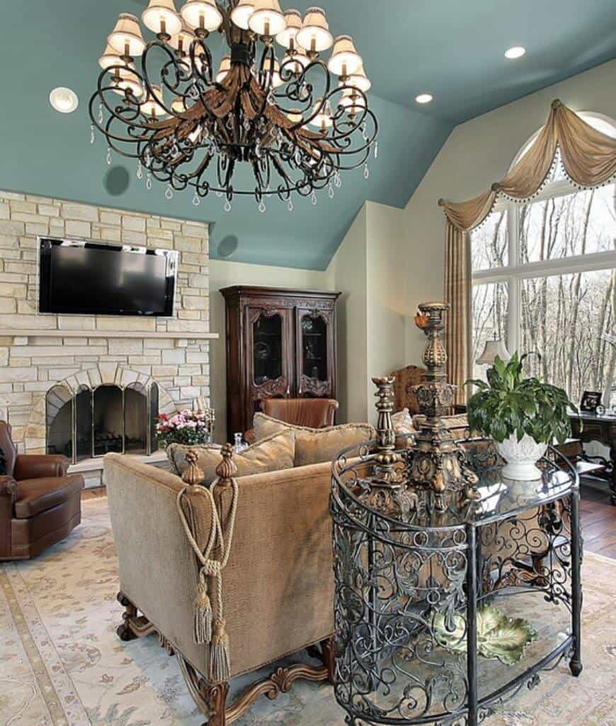 An ornate console table sits behind the gray sofa in this living room with leather armchairs and brick fireplace lighted by an oversized chandelier and recessed lights mounted on the vaulted ceiling.