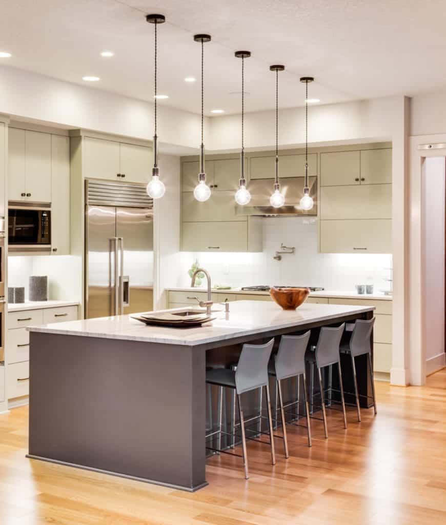 A series of mini glass globe pendants hang over the breakfast island in this kitchen with sleek cabinetry and gray counter chairs over hardwood flooring.