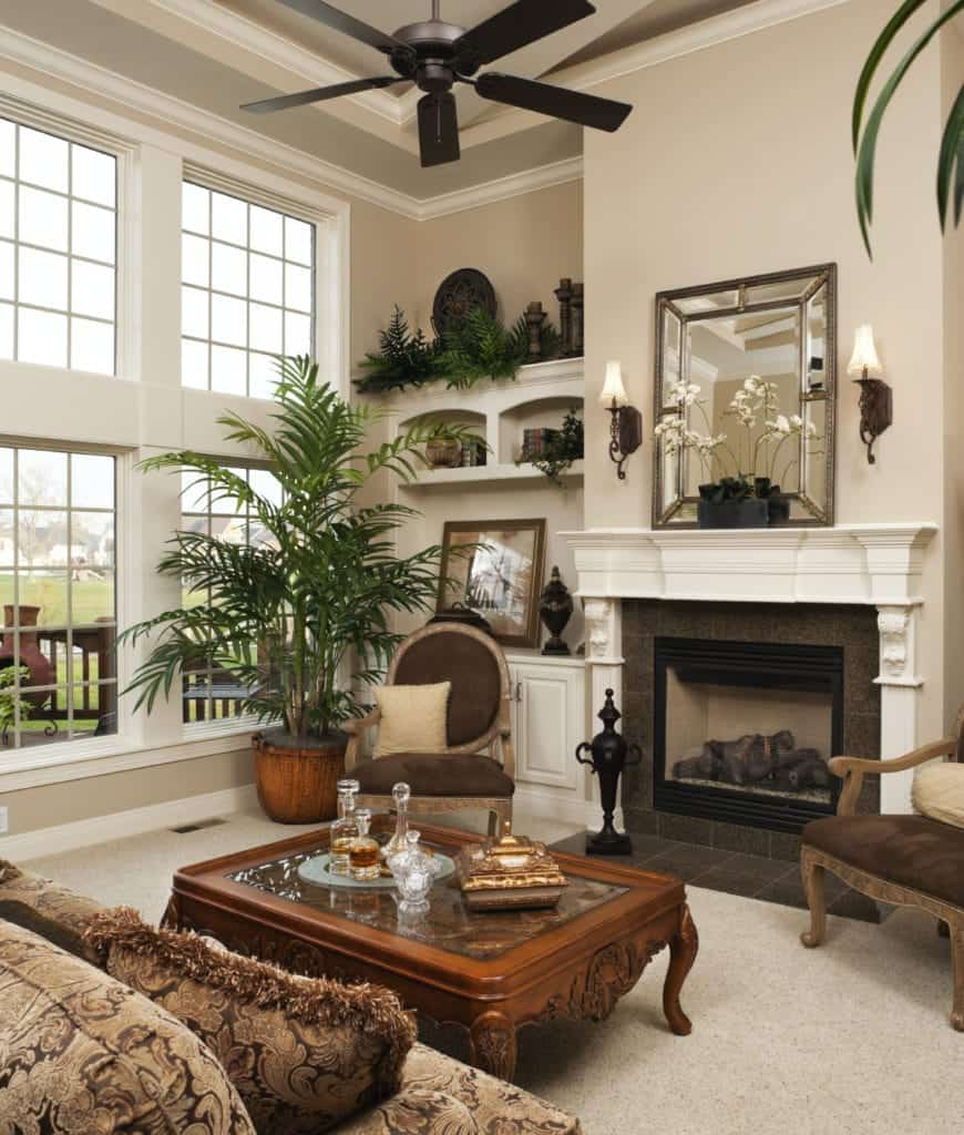 Tropical living room boasts a carved wooden coffee table and a fireplace with gray granite surround tiles framed with white mantel.
