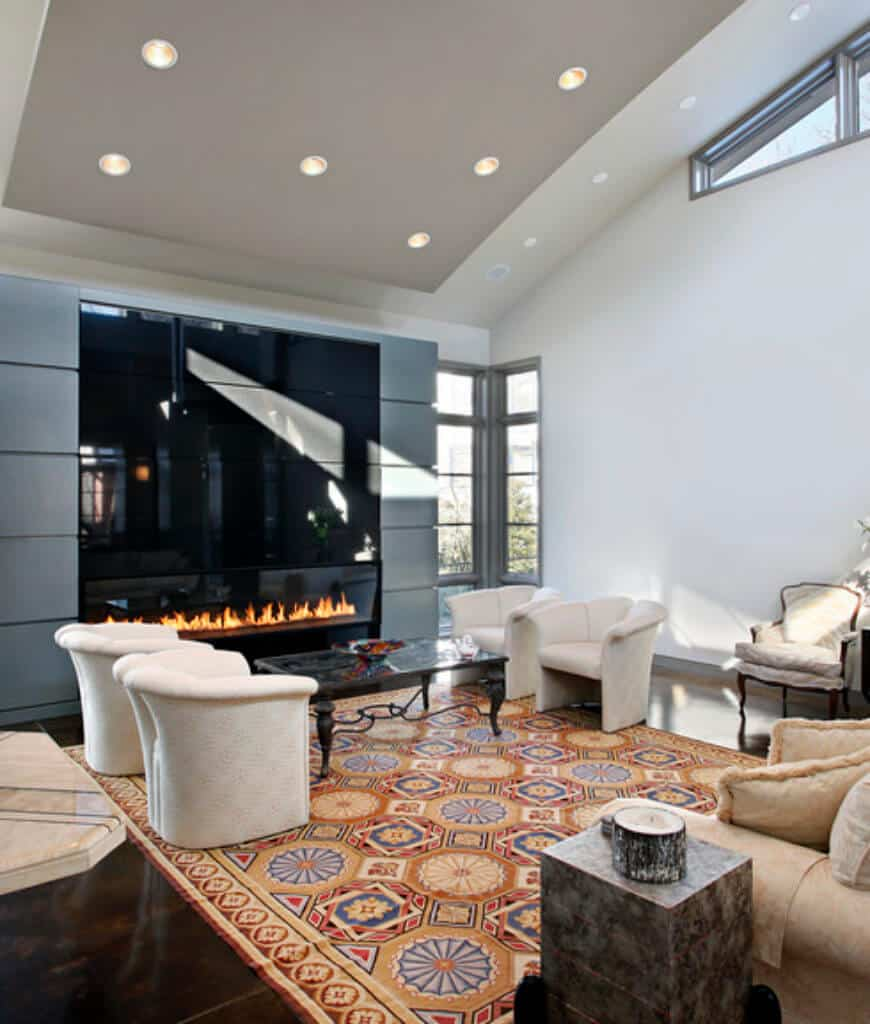 Modern living room with luxury fireplace and a metal coffee table in between beige round back chairs that sit on an eye-catching patterned rug. It is illuminated by recessed lights fitted on the gray vaulted ceiling.