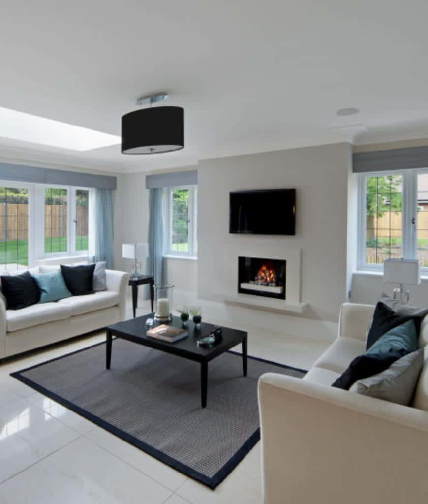 A black drum semi flush mount light illuminates this living room along with natural light from the framed glass windows. It has white sofas and a black coffee table facing the sleek fireplace.