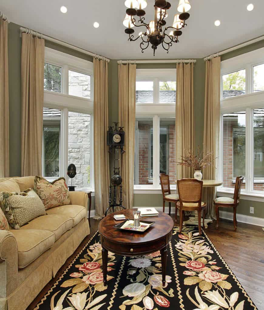 Charming living room boasts a skirted sectional and an oval coffee table that sits on a gorgeous floral rug. It includes an ornate chandelier and seating area by the glazed windows covered with beige draperies.