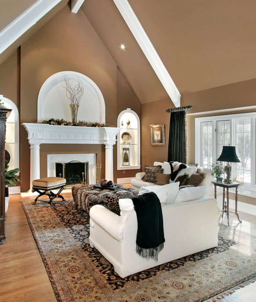 Brown living room with cathedral ceiling and hardwood flooring topped by a vintage rug. It has a fireplace with arched inset walls on the sides and white sofas contrasted with black throw blanket and drapery.