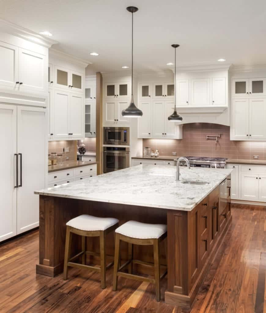 White cushioned stools sit at an immense breakfast island in this kitchen with white cabinetry and black dome pendants.