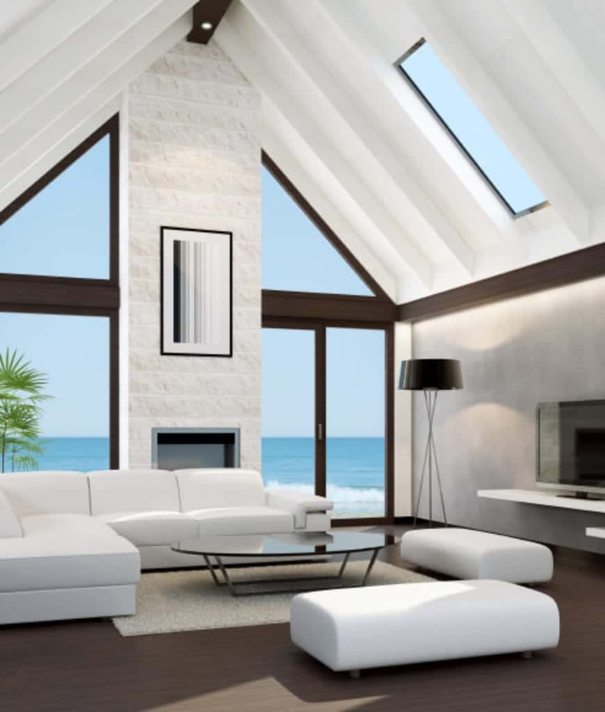 Sleek living room with white sofas and benches surrounding a glass top coffee table. It includes a cathedral ceiling and glass paneled windows overlooking a stunning beach view.