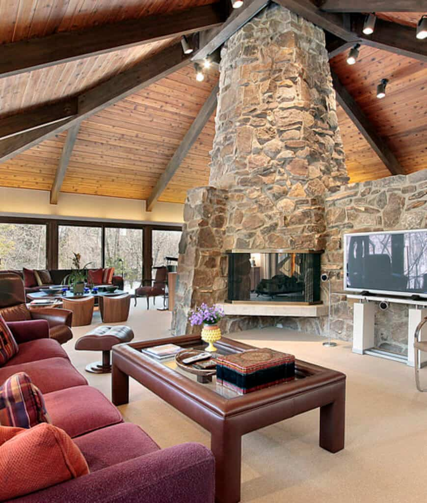 Southwestern living room features a fireplace fitted on the stone pillar that's attached to the wood plank ceiling lined with wood beams and fixed with track lights.