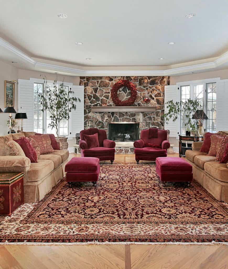Charming living room accented with red stools and velvet armchairs that sit in front of the fireplace fitted on the flagstone accent wall. It has a Persian rug and brown sectionals illuminated by recessed lights fixed to the tray ceiling.