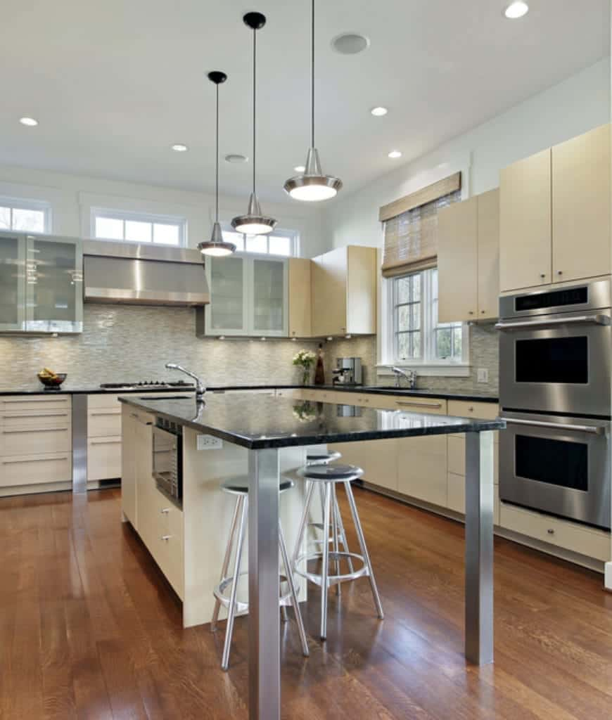This kitchen features a granite top breakfast island lighted by chrome pendants and surrounded with white cabinetry and a stainless steel double wall oven.