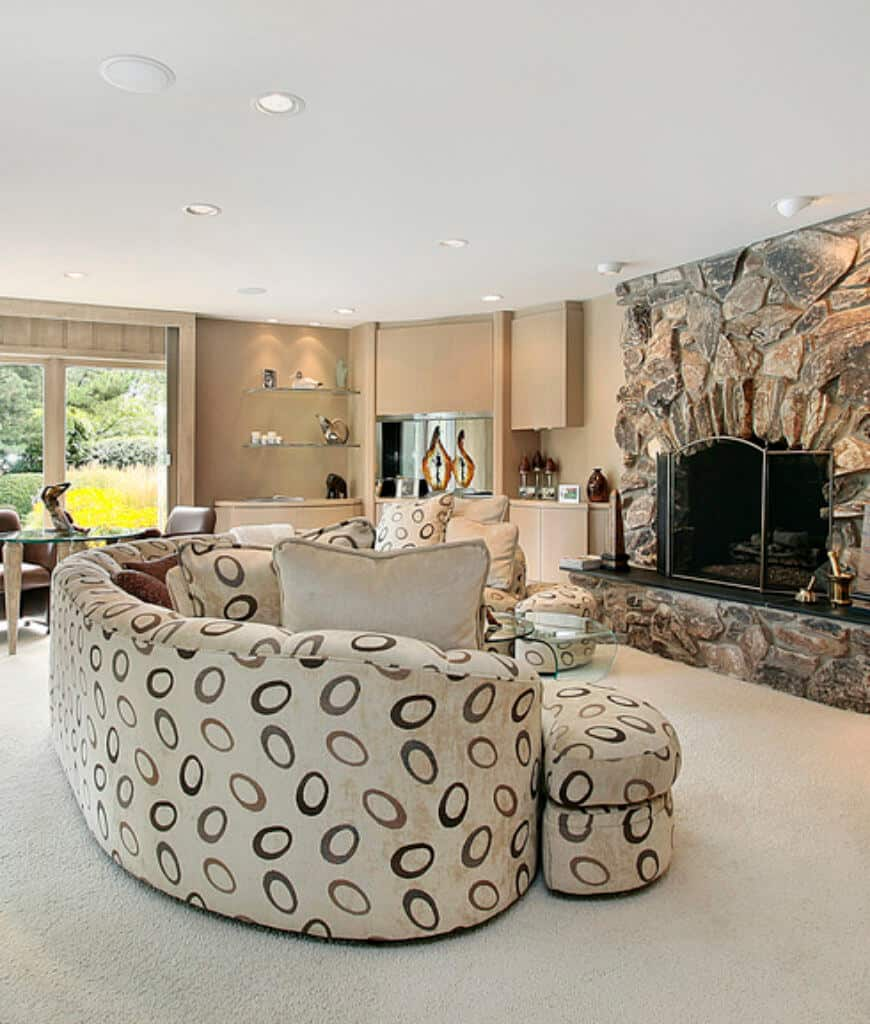 Fabulous living room showcases a curved patterned sofa and stone fireplace covered with a three-panel screen. It has carpet flooring and open shelving filled with contemporary decors.