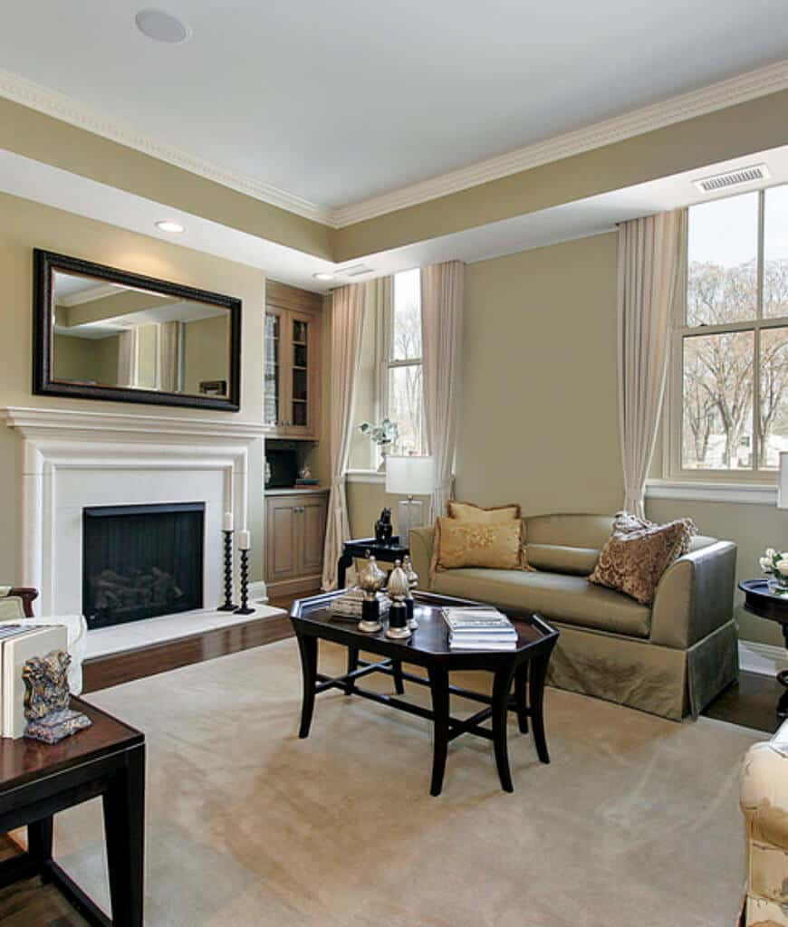 Formal living room features a skirted sofa and octagon coffee table that sits across the fireplace topped with a rectangular mirror.