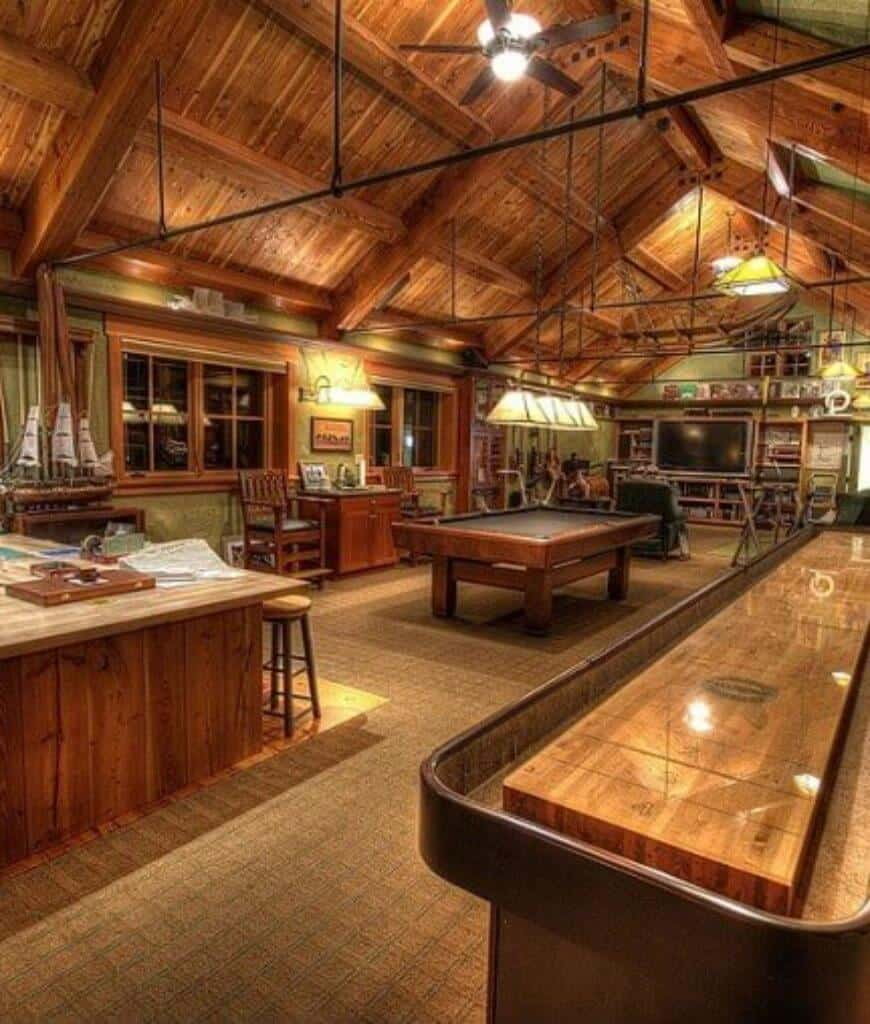 This entertainment room showcases carpet flooring and cathedral ceiling framed with metals and wood beams. There's a pool table in the middle surrounded with wooden furniture.