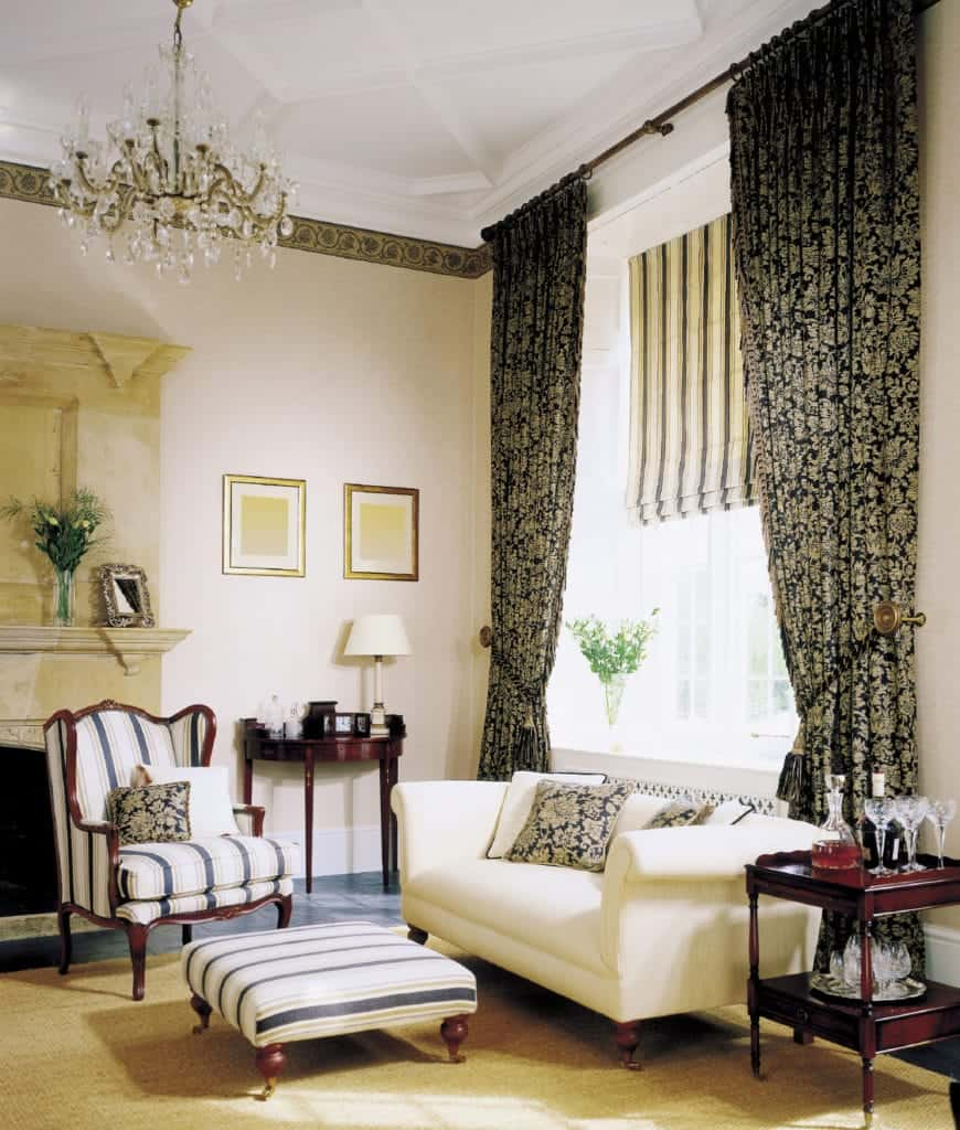 Victorian living room features a white sofa and striped wingback chair with matching ottoman. It has a white coffered ceiling with a hanging crystal chandelier and glazed window covered in striped roman shade and classy draperies.