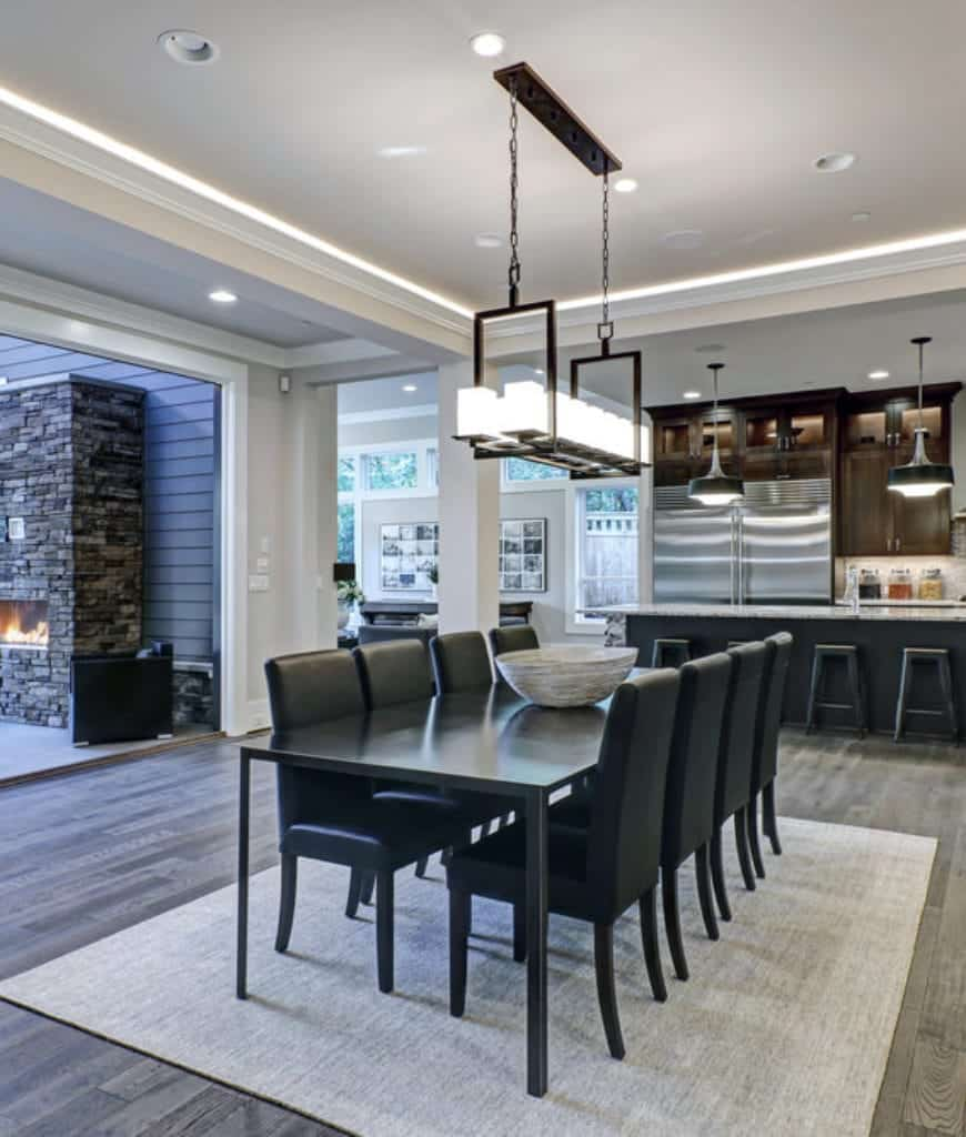 Black leather dining chairs sit at a metal table in this open dining area showcasing a linear chandelier and distressed rug over wood plank flooring.