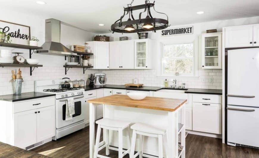 Farmhouse kitchen boasts a central breakfast island with white bar stools and wooden countertop illuminated by black pendant lights attached to the wrought iron pot rack.