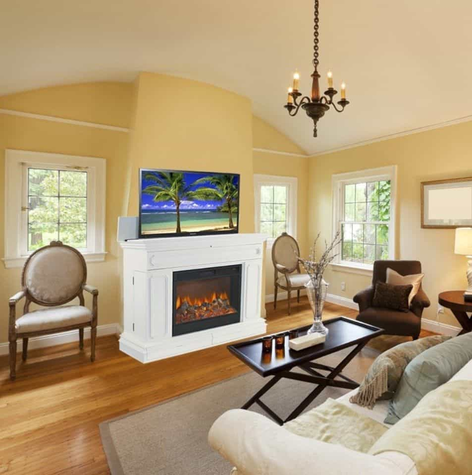 Yellow living room with a white fireplace and flat panel TV in between beige round back chairs. It is illuminated by a vintage chandelier that hung from the arched ceiling.