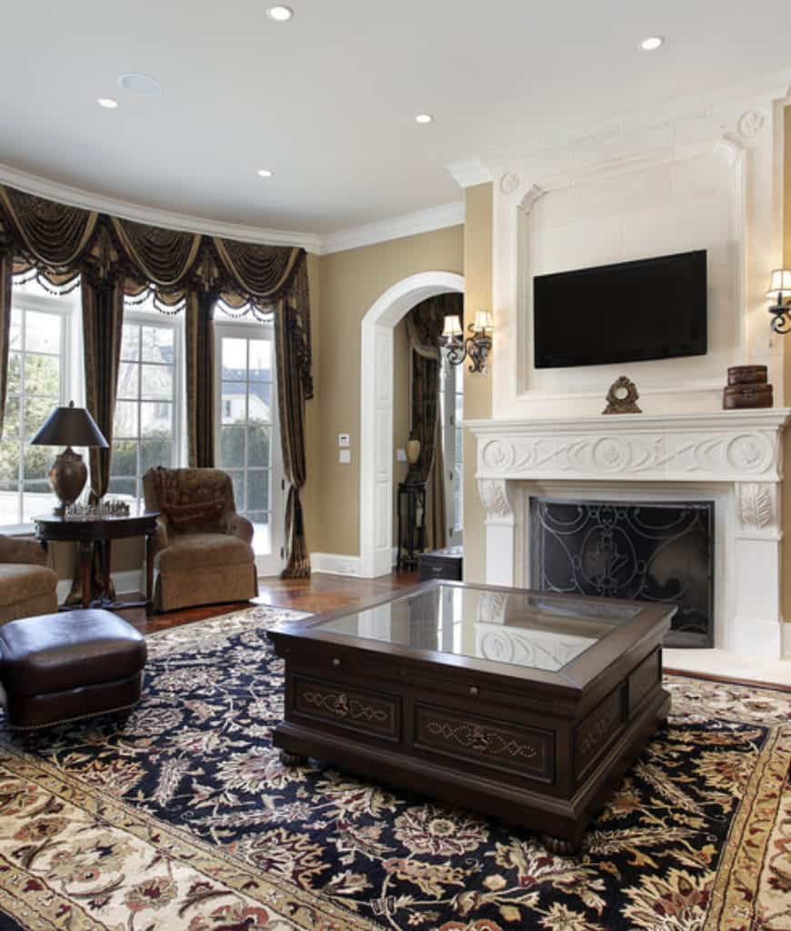 The sophisticated living room showcases a dark wood coffee table and a fireplace framed with ornate mantel and metal screen. There's a seating area by the full height windows covered in classy draperies and valences.
