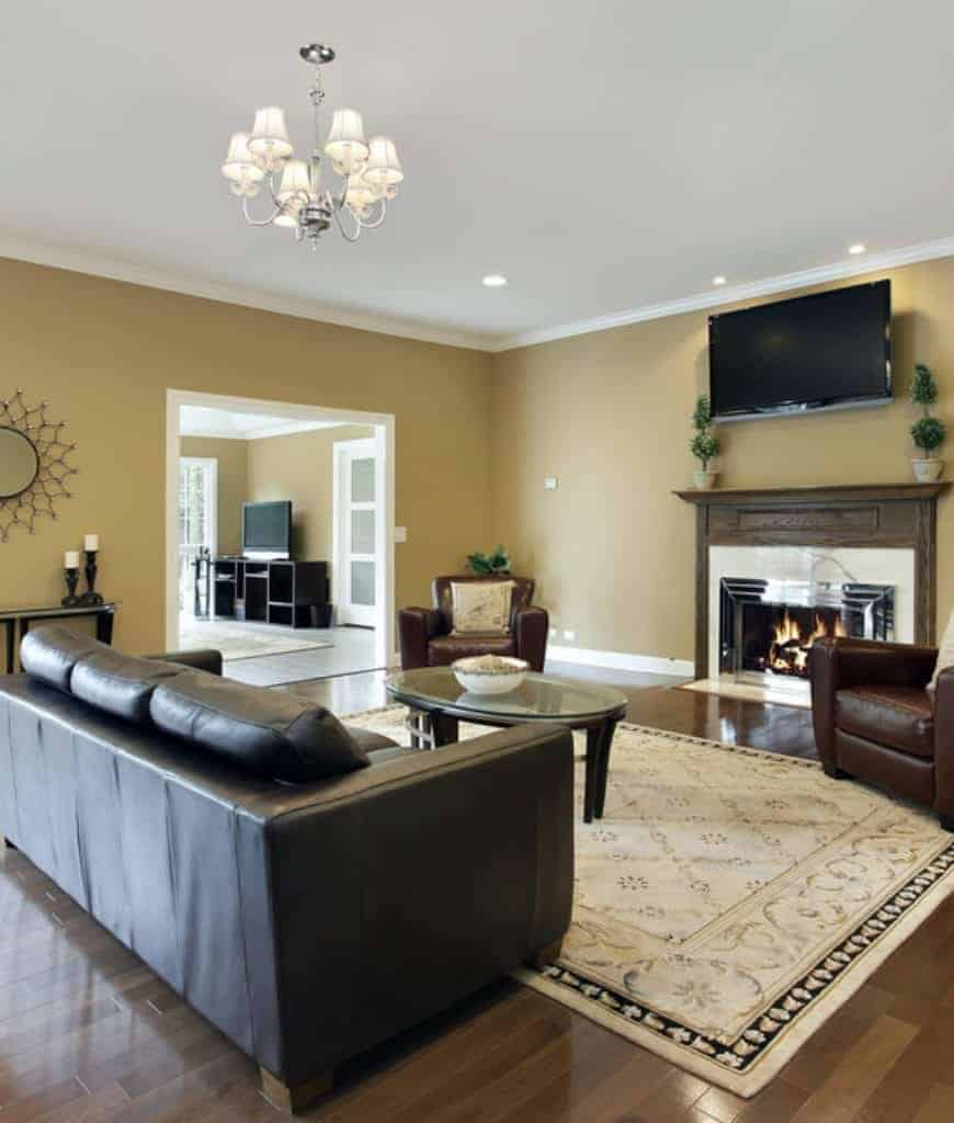A black leather sofa faces the oval coffee table and a wooden fireplace in this living room with television and white chandelier.