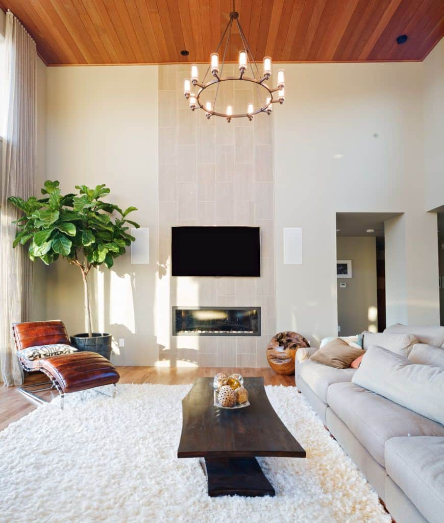 Fresh living room with a gray sectional and leather lounge chair paired with a dark wood coffee table over a white shaggy rug illuminated by a round pendant that hung from the wood plank ceiling.