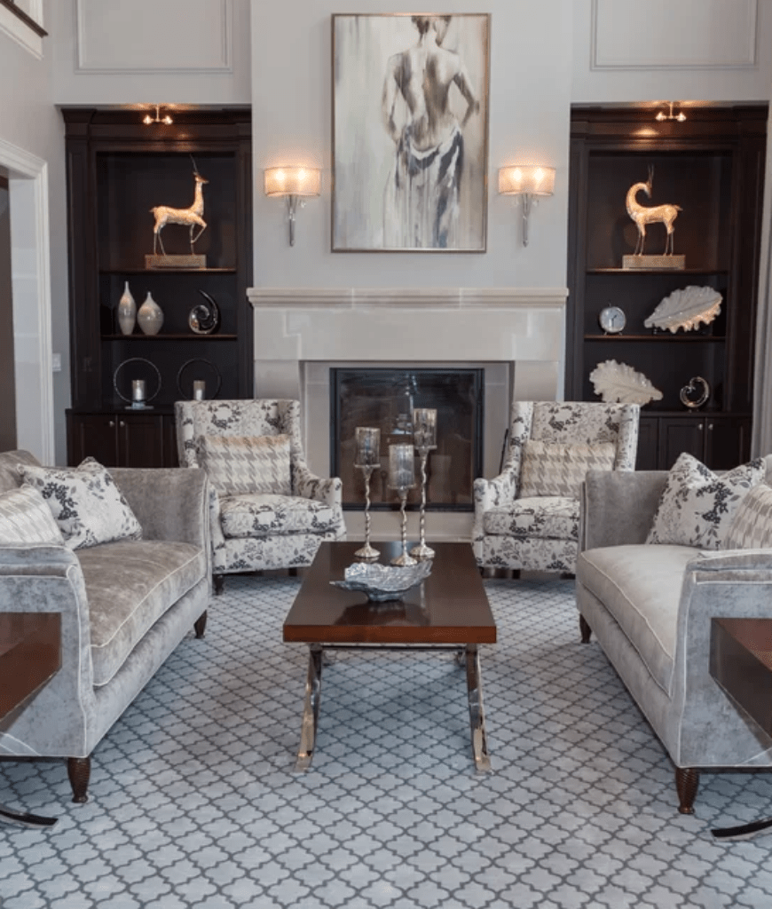 Gorgeous living room decorated with a lovely wall art that's mounted above the fireplace lighted by wall sconces. It has a wooden coffee table surrounded with gray velvet sofas and floral wingback chairs over a patterned rug.