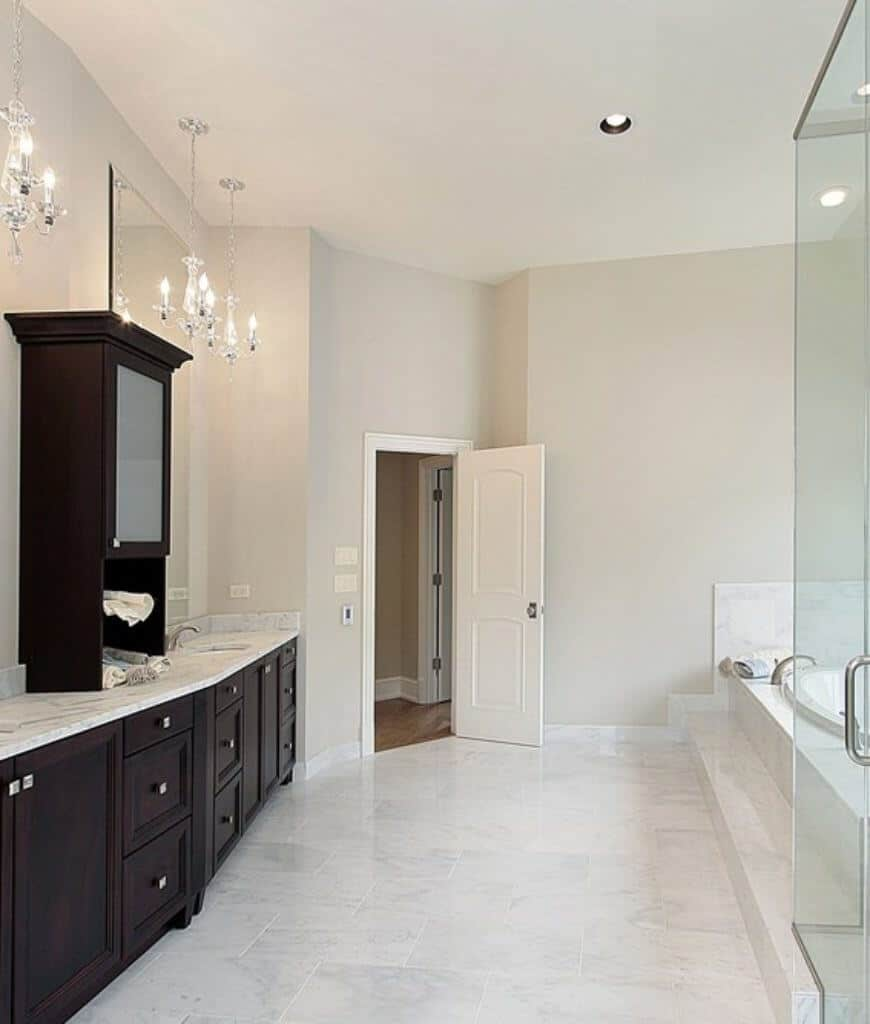 Classy primary bathroom highlighted with chrome chandeliers that hung over the dark wood sink vanity that's topped with a marble counter complementing with the tiled flooring.