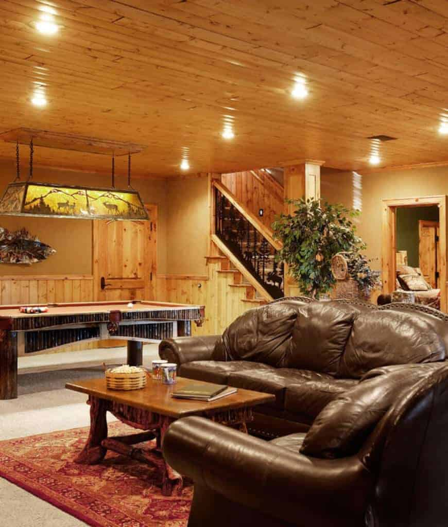 Cozy basement offers brown leather couches with a wooden coffee table and a pool table on the side lighted by a linear chandelier.