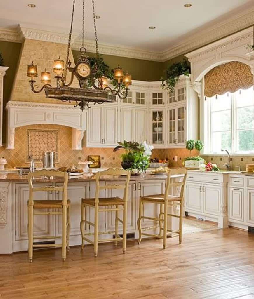 Charming kitchen offers a white breakfast bar lined with wooden chairs and lighted by a vintage chandelier. It has wood plank flooring and white framed windows dressed in gorgeous valence.