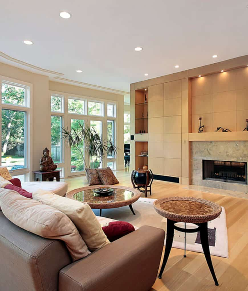 Warm living room with wood plank flooring and glass paneled windows overlooking the outdoor greenery. It has round tables and brown sofa facing the fireplace framed with marble surround tiles.