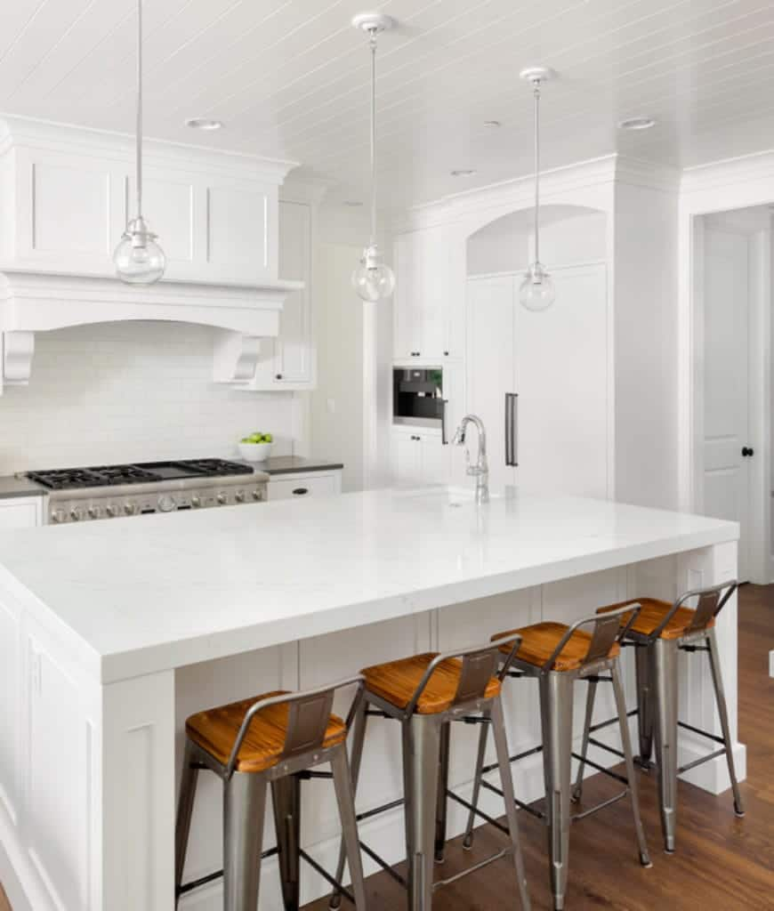 Wooden bar stools stand out in this clean white kitchen offering stainless steel appliances and glass globe pendants that hung over the breakfast island.