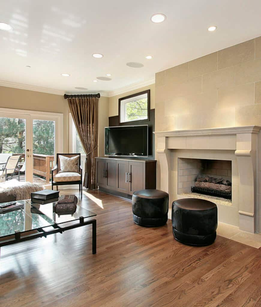 A pair of black leather stools sit in front of the brick fireplace in this living room with a glass top coffee table and flat panel TV mounted on the built-in cabinet.