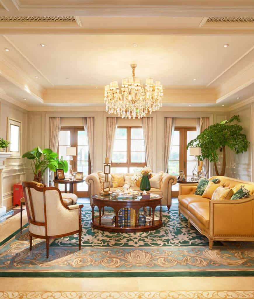 This living room features leather seats and a round coffee table over a green rug lighted by a fancy chandelier that hung from the tray ceiling.
