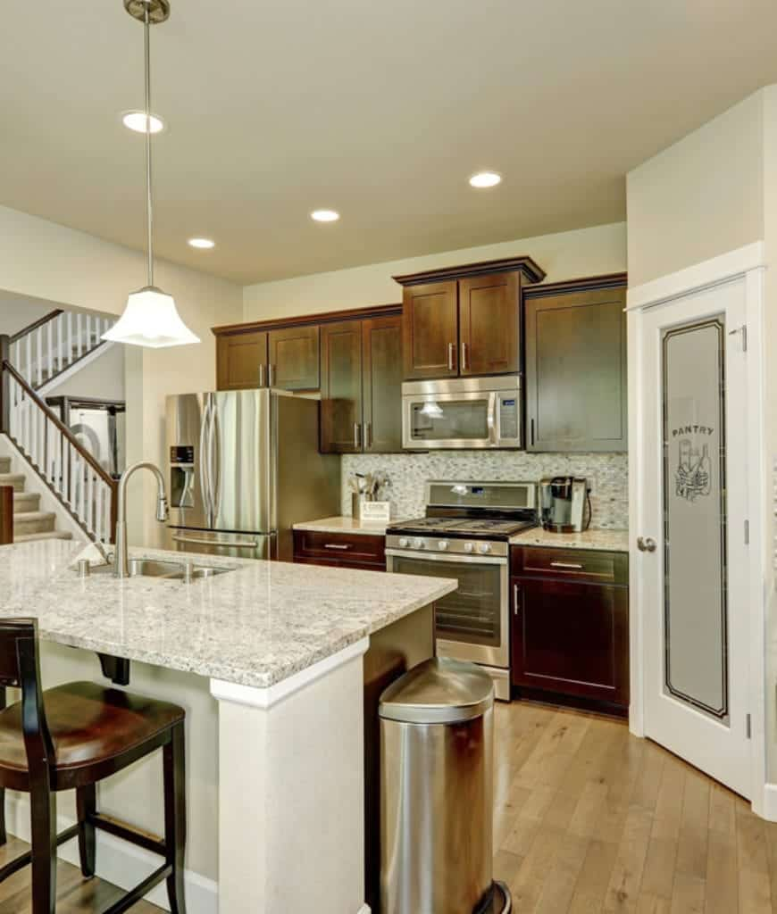 This kitchen showcases stainless steel appliances and granite countertops matching with the backsplash tiles. It has wood plank flooring and a white door that leads to the pantry.