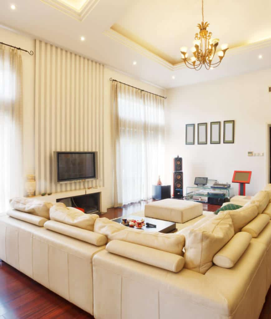 Cream living room with rich hardwood flooring and full height windows covered with sheer curtains. It is illuminated by a brass chandelier that hung from the tray ceiling.