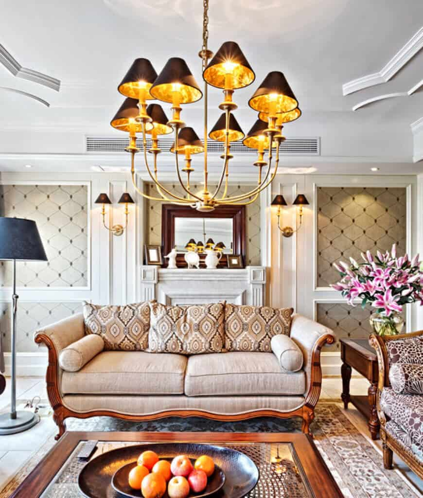 Fabulous living room clad in classy wallpaper and illuminated by a brass chandelier and matching sconces fixed on the white wainscoting.