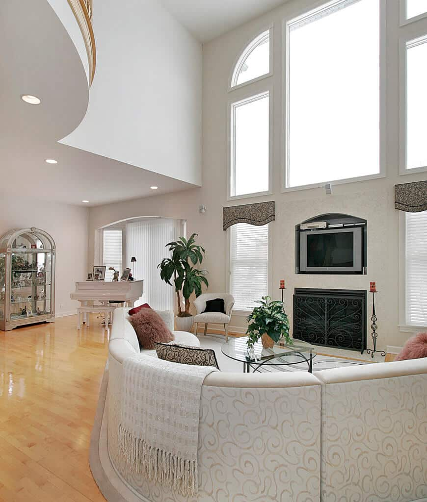 Elegant living room with polished hardwood flooring and louvered windows dressed in classy valences. It has a curved sectional and round glass top coffee table facing the fireplace wrapped in ornate wrought iron fence.