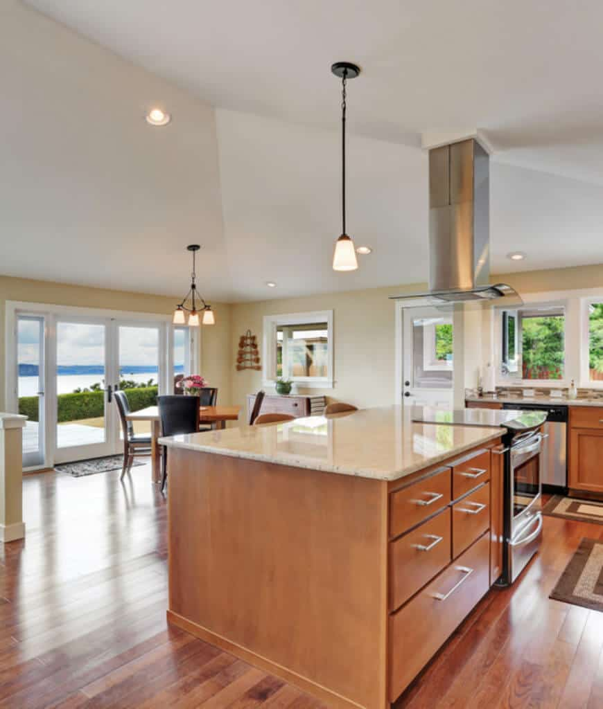 Cozy eat-in kitchen with wood plank flooring and a French door that opens to the yard overlooking a breathtaking ocean view. It includes a vaulted ceiling mounted with recessed and pendant lights along with a sleek vent hood that stands over the cooktop.