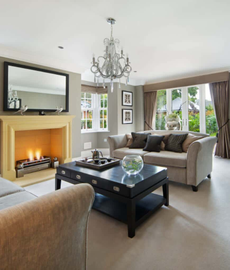 Formal living room showcases a mirror mounted above the yellow fireplace and a fabulous chandelier that hung over the black coffee table in between gray sofas that sit on a carpet flooring.